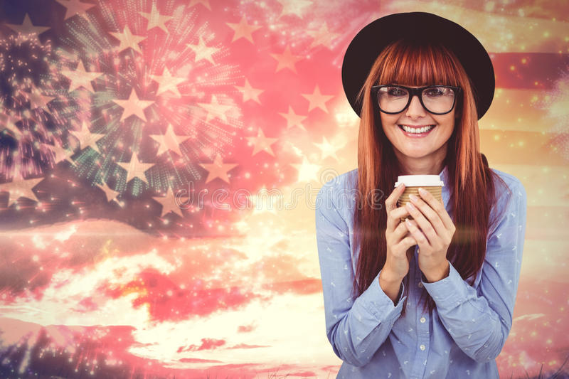 Composite image of smiling hipster woman drinking coffee. Smiling hipster woman drinking coffee against composite image of colourful fireworks exploding on black royalty free stock photo