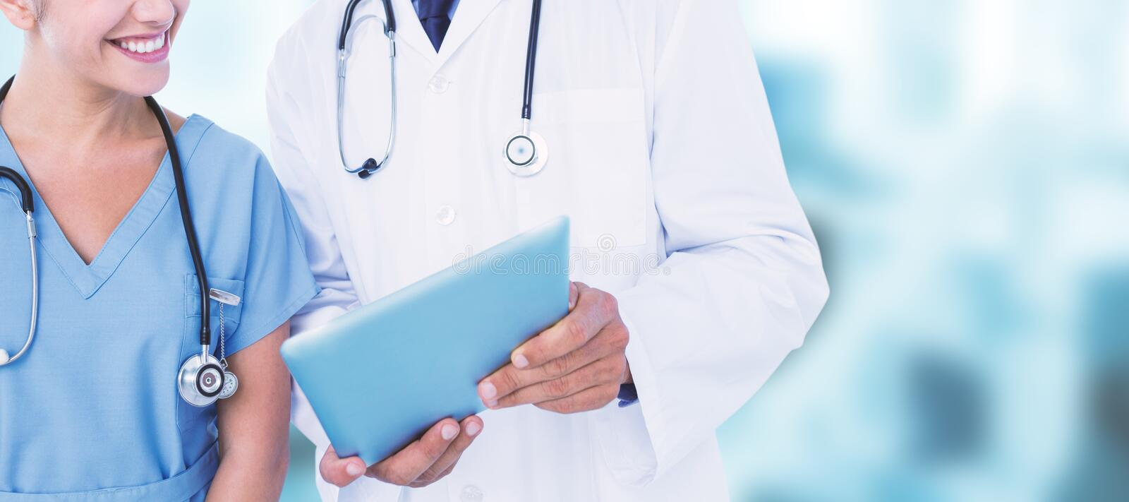 Composite image of smiling male doctor with nurse using digital tablet stock photo