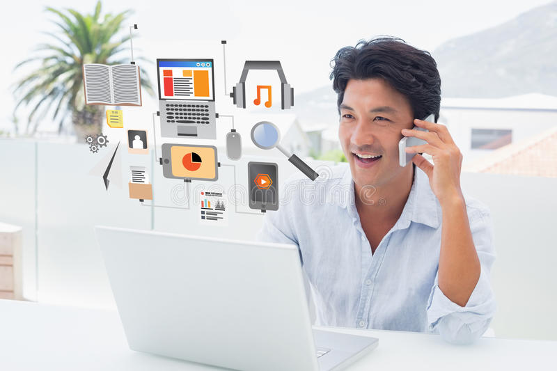 Composite image of smiling man using his laptop and talking on phone stock photography