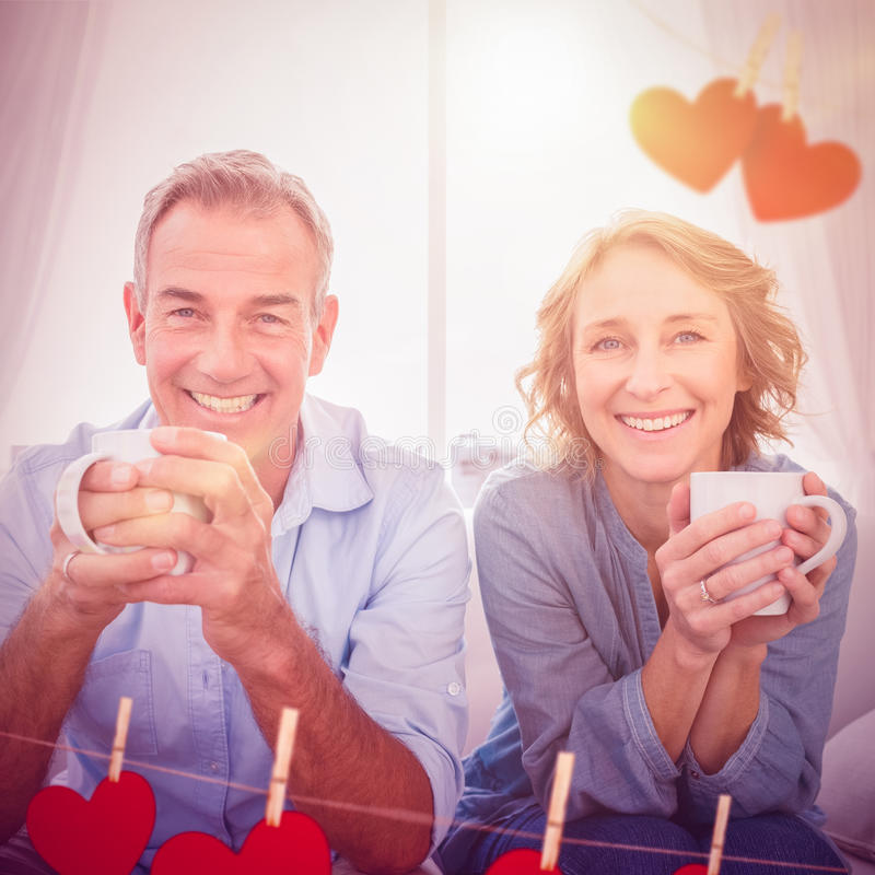 Composite image of smiling middle aged couple sitting on the couch having coffee royalty free stock images