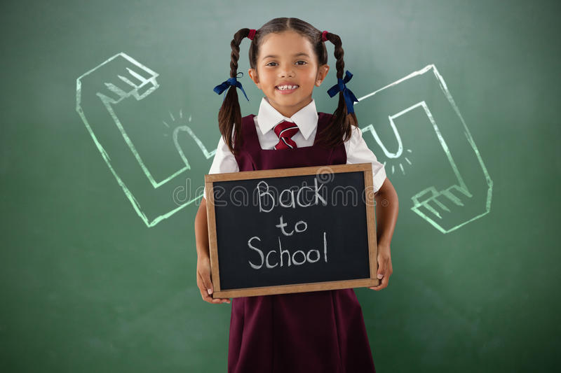 Composite image of smiling schoolgirl holding writing slate royalty free stock photo