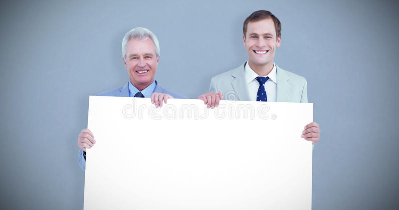 Composite image of smiling tradesmen holding blank sign. Smiling tradesmen holding blank sign against grey background royalty free stock images