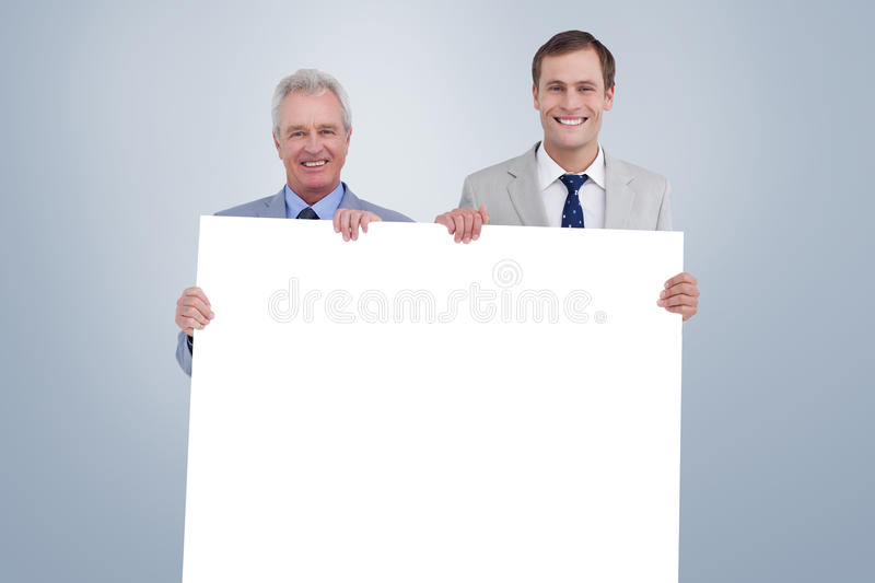 Composite image of smiling tradesmen holding blank sign. Smiling tradesmen holding blank sign against grey vignette royalty free stock photography