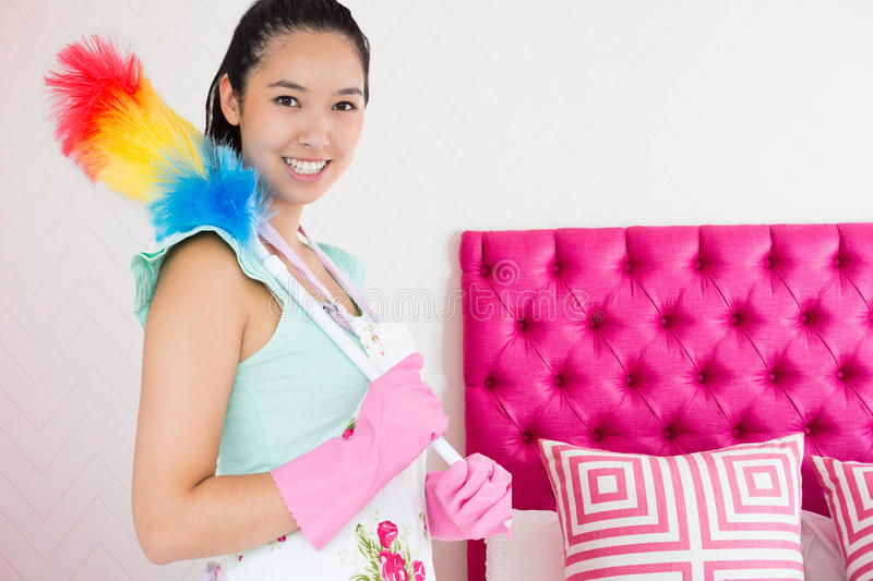 Composite image of smiling woman with duster royalty free stock photography