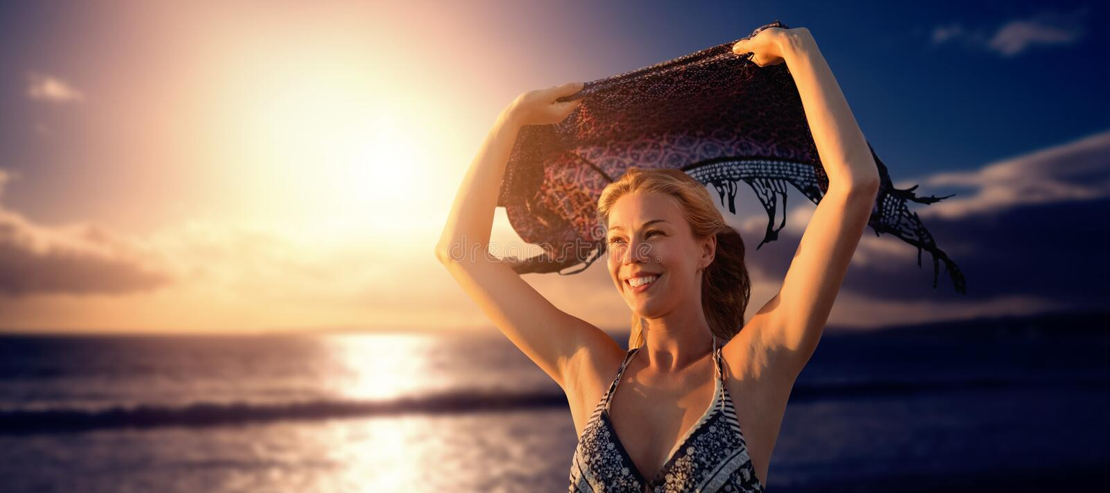 Composite image of smiling woman holding scarf in the air stock images