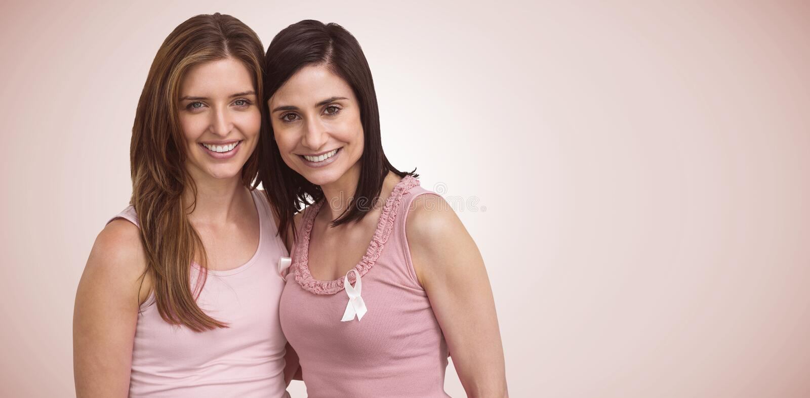 Composite image of smiling women in pink outfits posing for breast cancer awareness. Smiling women in pink outfits posing for breast cancer awareness against stock image