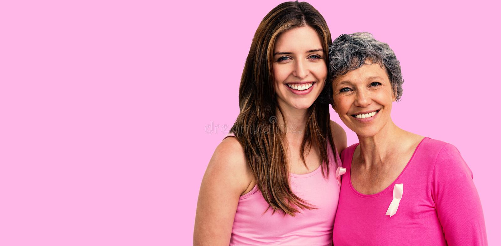 Composite image of smiling women in pink outfits posing for breast cancer awareness. Smiling women in pink outfits posing for breast cancer awareness against royalty free stock images