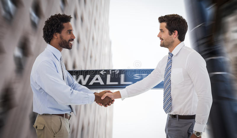Composite image of smiling young businessmen shaking hands in office. Smiling young businessmen shaking hands in office against wall street stock photos