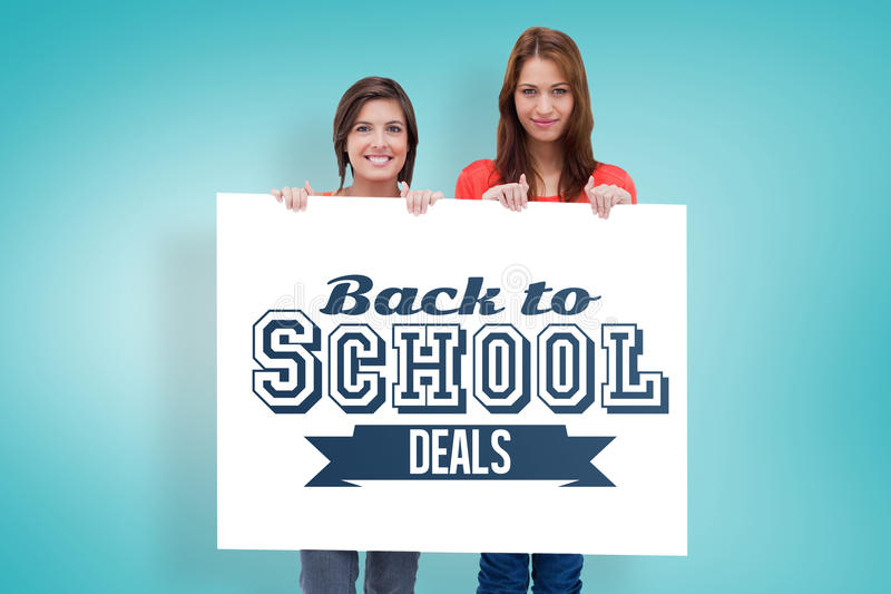 Composite image of smiling young women proudly holding a blank poster. Smiling young women proudly holding a blank poster against blue vignette background royalty free stock images