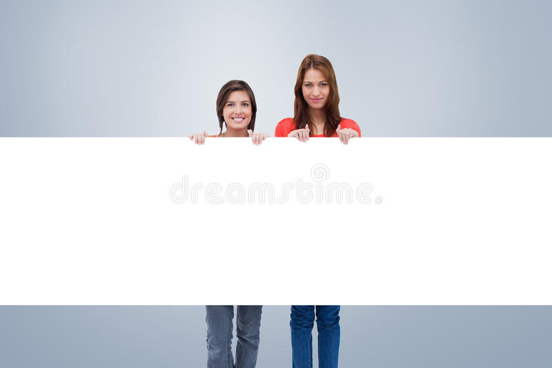 Composite image of smiling young women proudly holding a blank poster royalty free stock photography