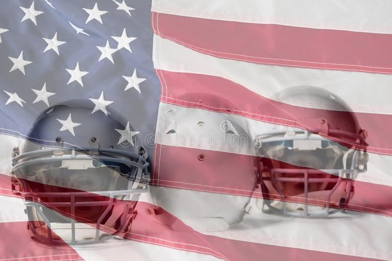 Composite image of sports helmet arranged side by side. Sports helmet arranged side by side against close-up of an american flag stock image