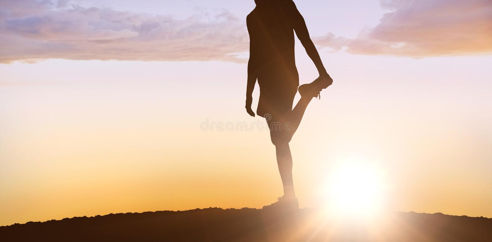 Composite image of sporty man stretching his leg stock photography