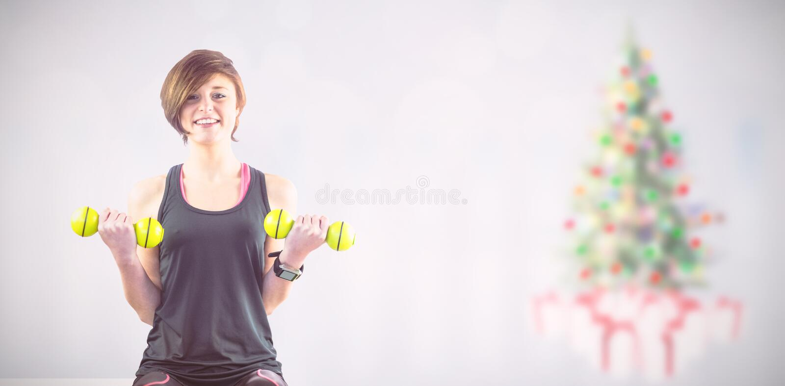 Composite image of sporty woman smiling while lifting dumbbells royalty free stock photo