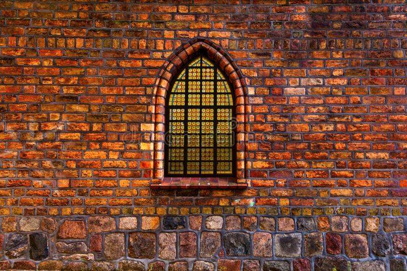 Glowing stained glass window on an ancient church. Composite image of stained glass window set in ancient window arch of an old church stock photos