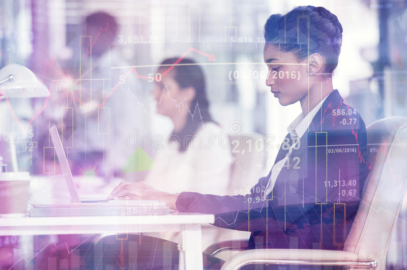 Composite image of stocks and shares. Stocks and shares against focused businesswoman working on laptop royalty free stock photos