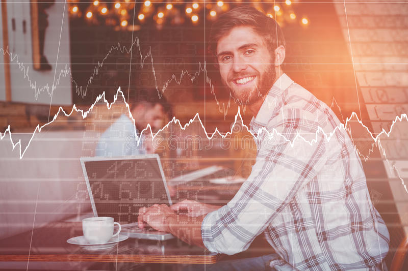 Composite image of stocks and shares. Stocks and shares against young men working on his computer royalty free stock photography