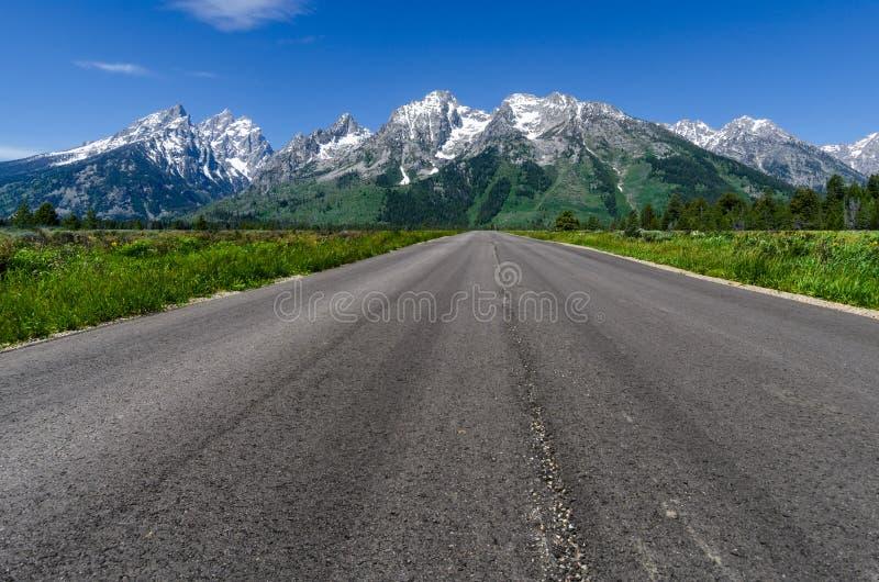 Straight road to Teton mountain range royalty free stock images
