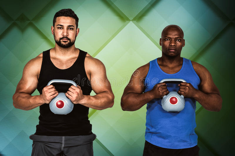 Composite image of strong friends lifting kettlebells together stock photo