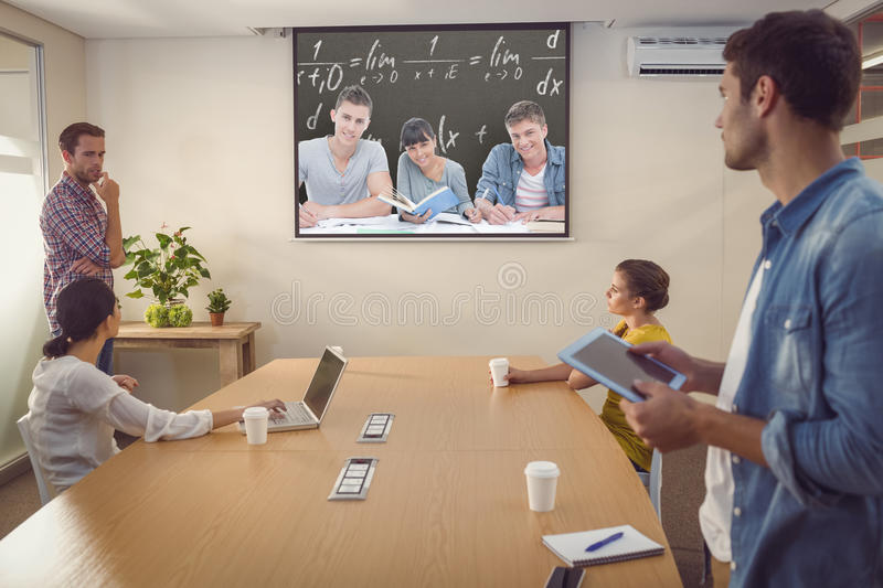 Composite image of students doing work together as they all look into the camera stock photo