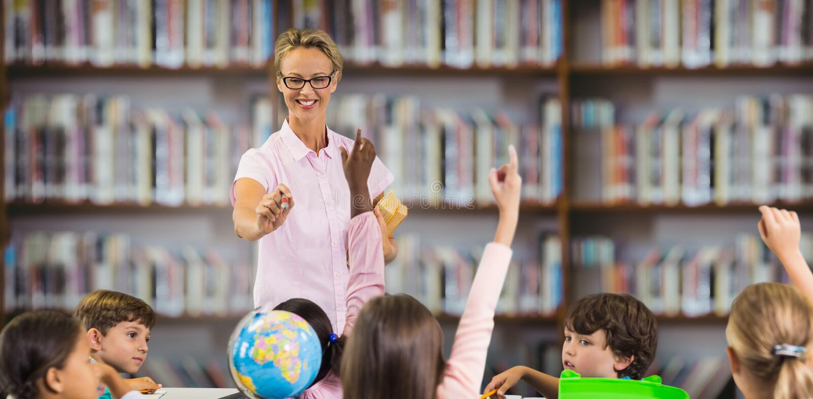 Composite image of students raising hands while teacher teaching stock photo