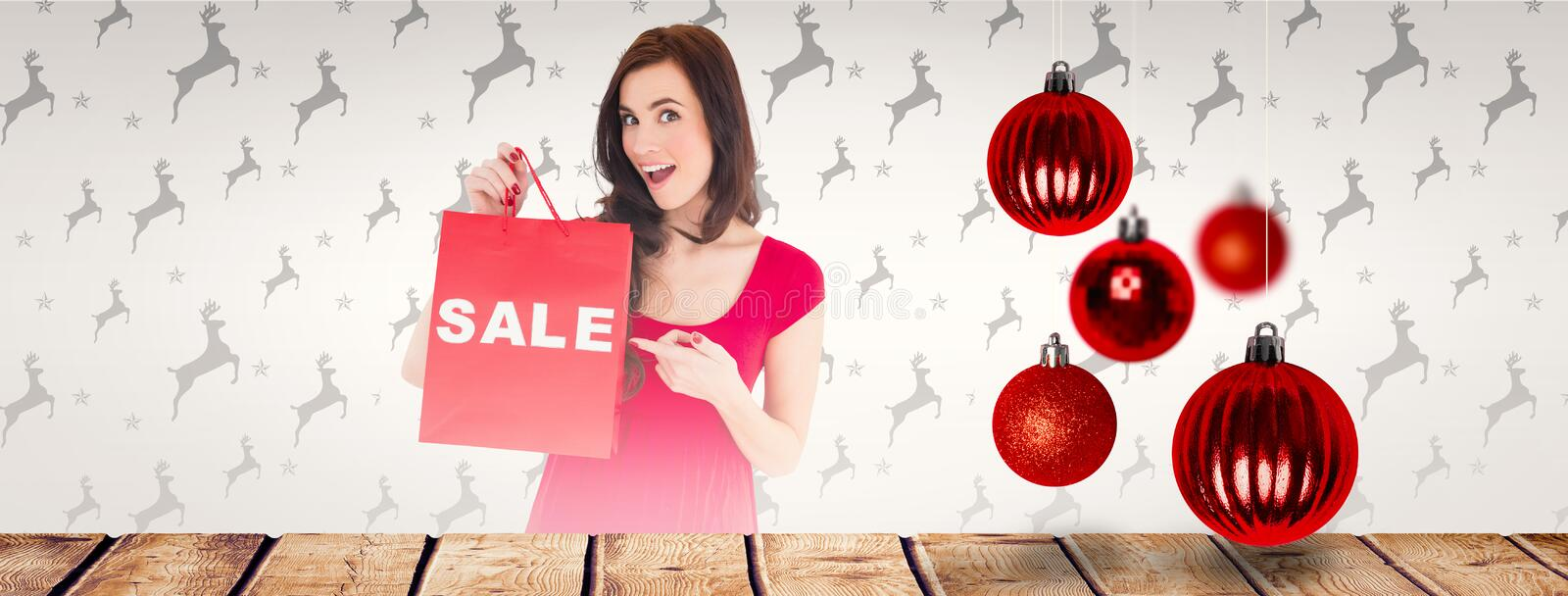 Composite image of stylish brunette in red dress showing sale bag. Stylish brunette in red dress showing sale bag against christmas baubles royalty free stock photos
