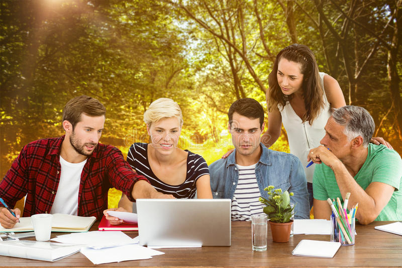 Composite image of teamwork using laptop together. Teamwork using laptop together against path in woods royalty free stock image