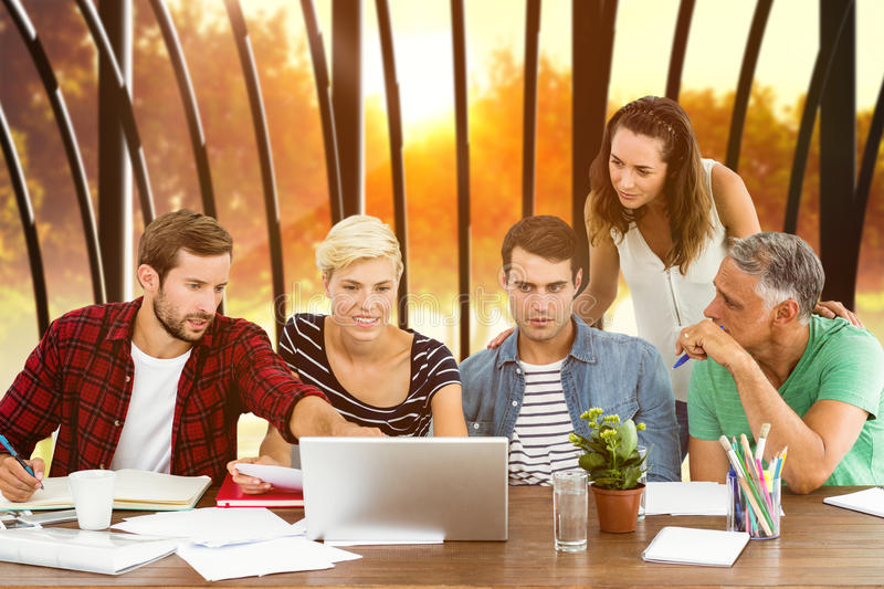 Composite image of teamwork using laptop together. Teamwork using laptop together against sunrise over trees stock image