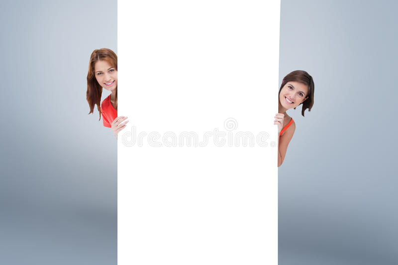 Composite image of teenage girls hiding behind a blank poster while showing their head from each sid. Teenage girls hiding behind a blank poster while showing stock photos