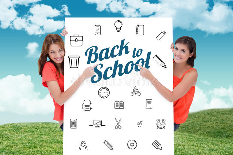 Composite image of teenage girls looking at the camera while pointing their fingers on a blank poste. Teenage girls looking at the camera while pointing their royalty free stock images