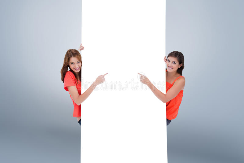 Composite image of teenage girls looking at the camera while pointing their fingers on a blank poste. Teenage girls looking at the camera while pointing their stock photography