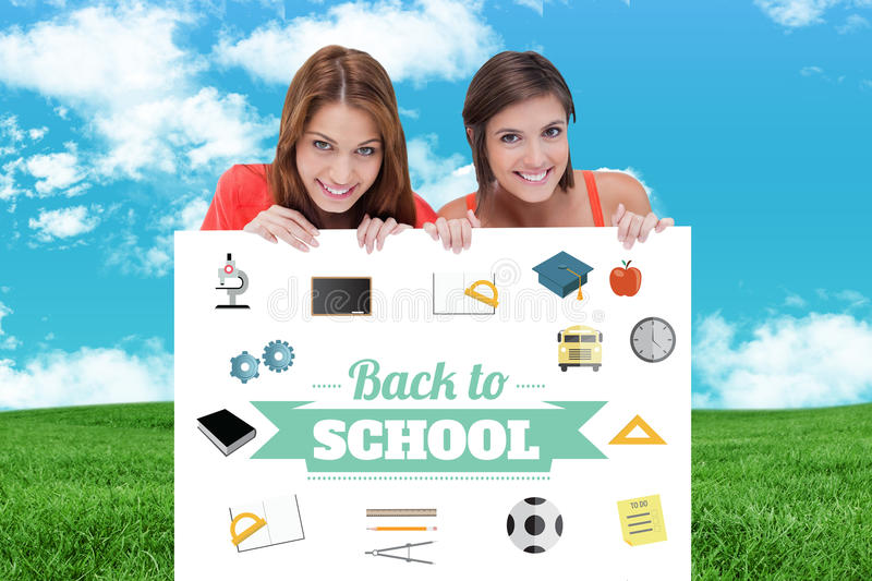Composite image of teenage girls smiling while holding a blank poster and hiding behind it. Teenage girls smiling while holding a blank poster and hiding behind royalty free stock photography