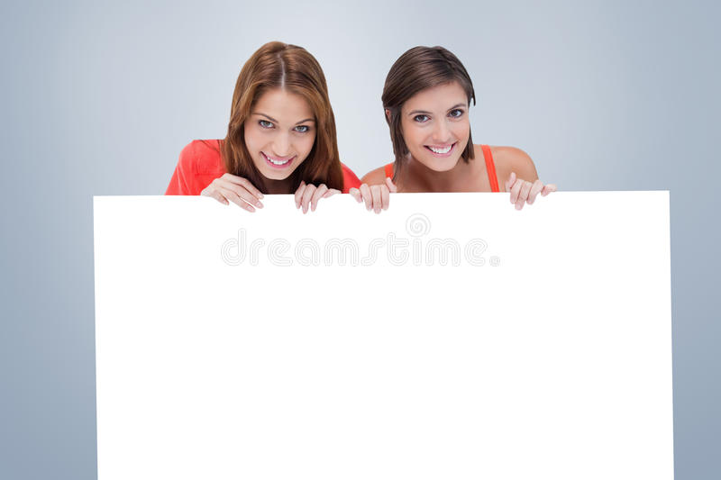 Composite image of teenage girls smiling while holding a blank poster and hiding behind it. Teenage girls smiling while holding a blank poster and hiding behind stock images