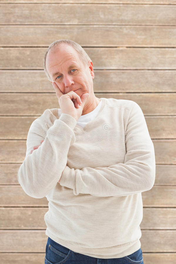Composite image of thinking mature man with hand on chin royalty free stock photo