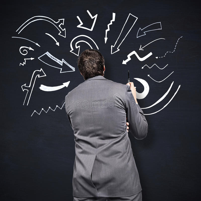 Composite image of thoughtful businessman holding pen. Thoughtful businessman holding pen against blackboard royalty free stock photo