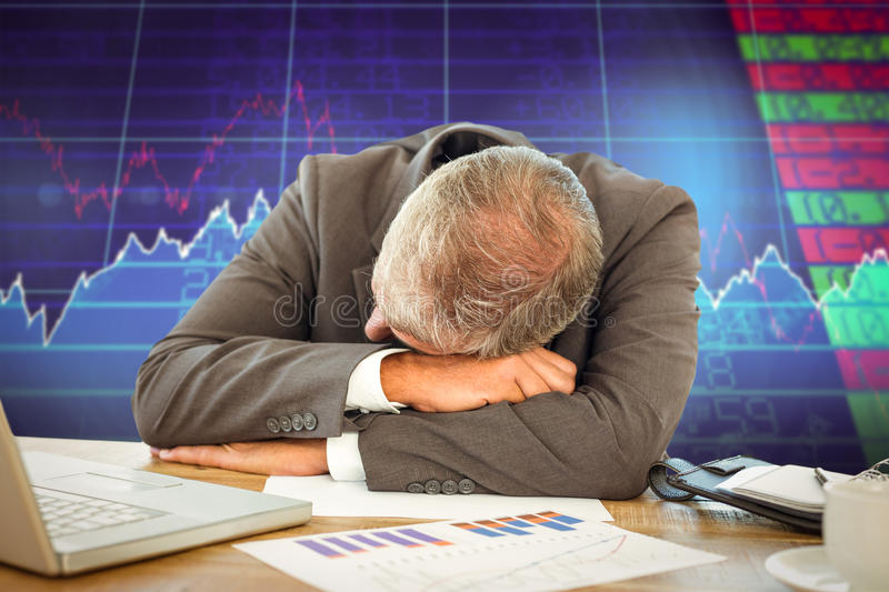 Composite image of tired businessman resting on desk. Tired businessman resting on desk against stocks and shares royalty free stock image