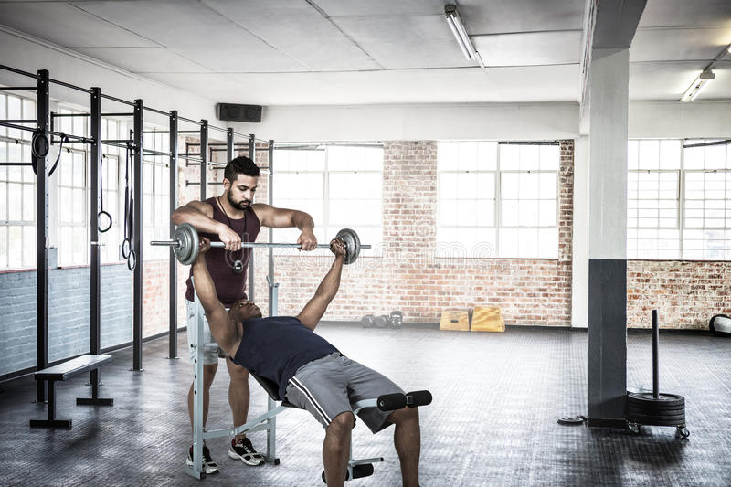 Composite image of trainer helping muscular man to lift the barbell stock images