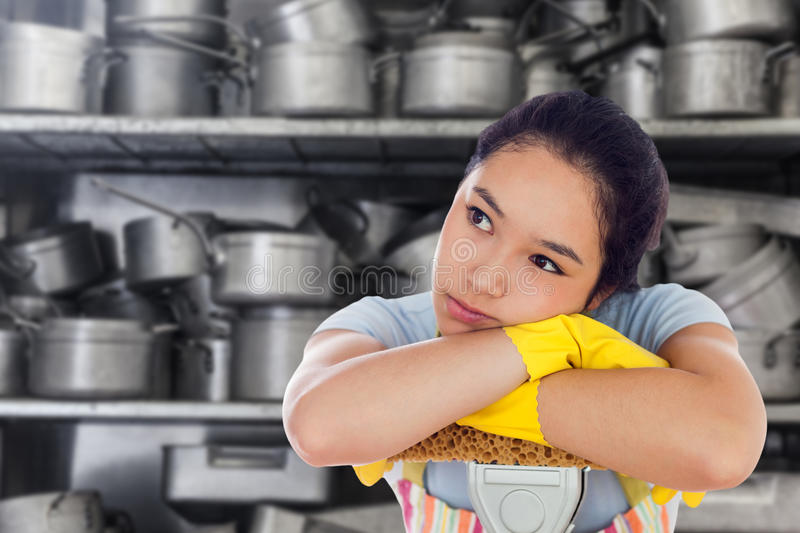 Composite image of troubled woman leaning on a mop. Troubled woman leaning on a mop against shelf full of pans stock images