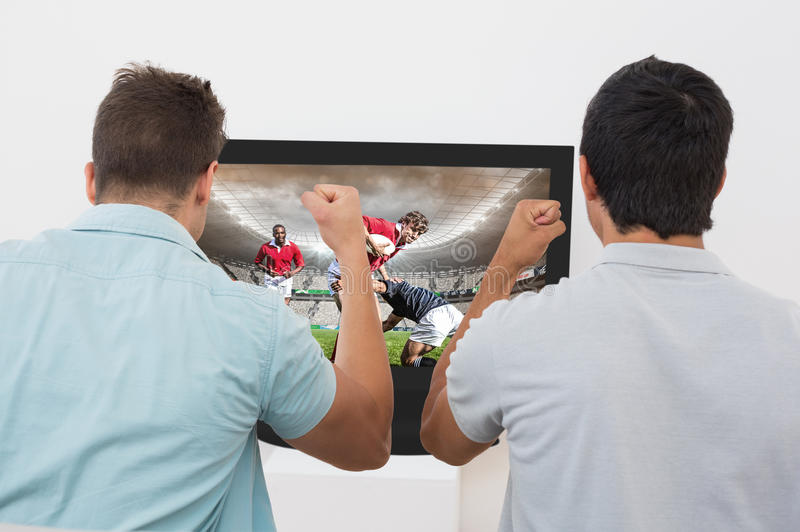 Composite image of two excited soccer fans watching tv. Two excited soccer fans watching tv against rugby players tackling during game stock illustration