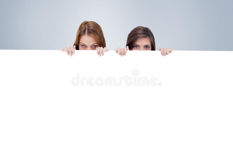 Composite image of two friends secretly hiding behind a blank poster. Two friends secretly hiding behind a blank poster against grey vignette royalty free stock photos