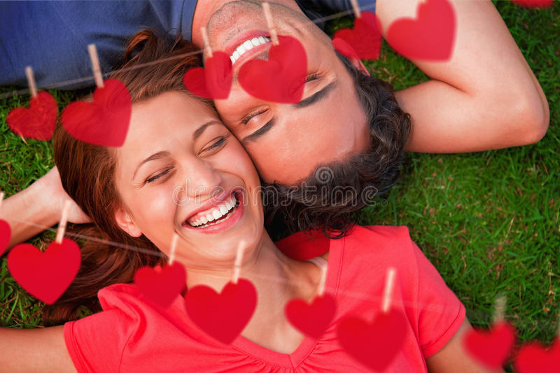 Composite image of two friends smiling while lying head to shoulder with an arm behind their head stock illustration