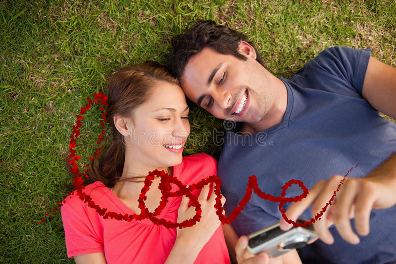 Composite image of two smiling friends looking at photos on a camera. Two smiling friends looking at photos on a camera against love spelled out in petals stock illustration