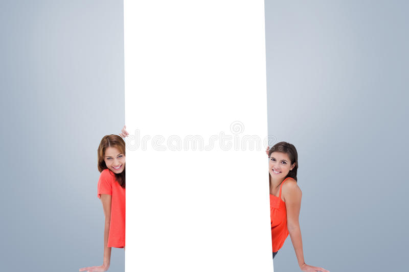 Composite image of two smiling teenage girls sitting behind a blank poster. Two smiling teenage girls sitting behind a blank poster against grey vignette stock image