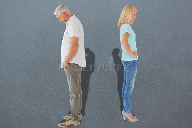 Composite image of unhappy couple not speaking to each other. Unhappy couple not speaking to each other against grey stock photos