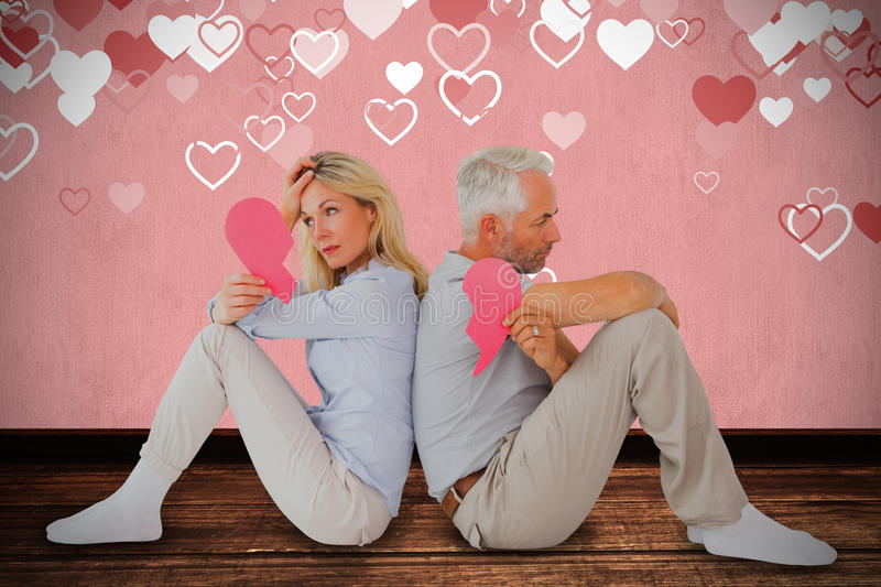 Composite image of unhappy couple sitting while holding broken heart. Unhappy couple sitting while holding broken heart against white background royalty free stock photo