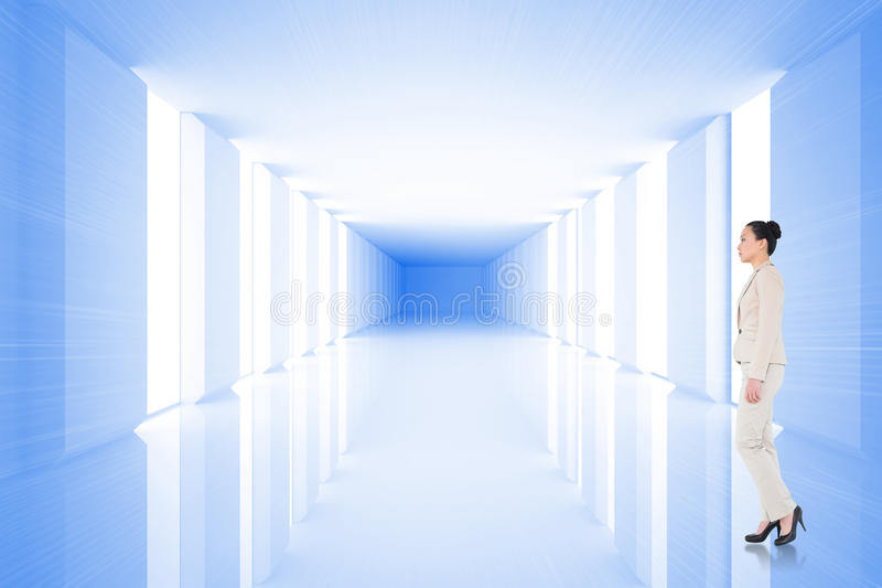Composite image of unsmiling asian businesswoman walking. Unsmiling asian businesswoman walking against bright blue room with windows royalty free stock photo