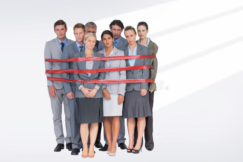 Composite image of upset business team fastened with adhesive tape. Upset business team fastened with adhesive tape against grey vignette stock image