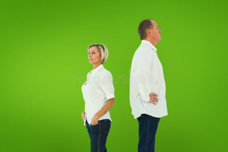 Composite image of upset couple not talking to each other after fight. Upset couple not talking to each other after fight against green vignette stock photography
