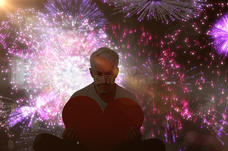 Composite image of upset man sitting holding heart shape. Upset man sitting holding heart shape against colourful fireworks exploding on black background royalty free stock photo