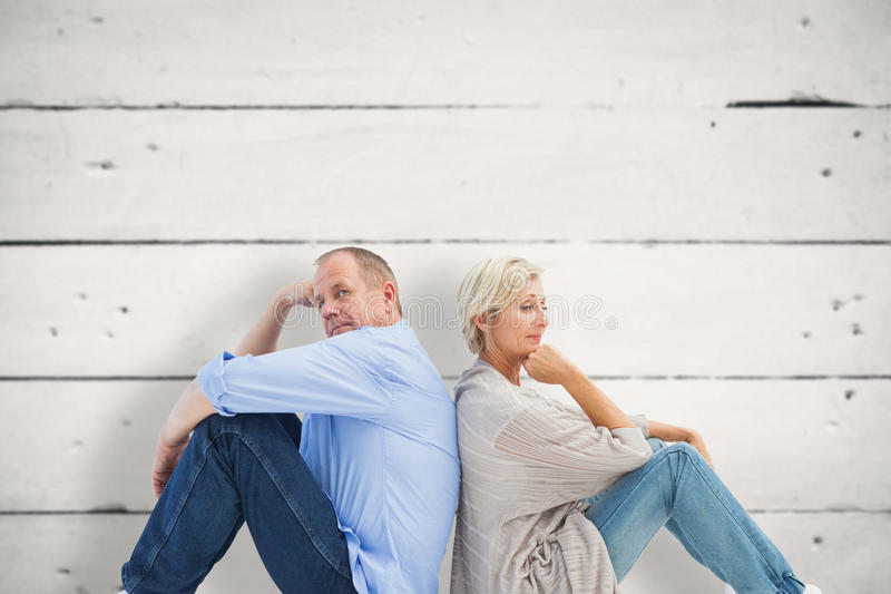 Composite image of upset mature couple not talking. Upset mature couple not talking against white wood stock images