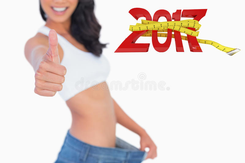 Composite image of victorious woman holding her too big pants thumbs up. Victorious woman holding her too big pants thumbs up against digitally generated image royalty free stock photography
